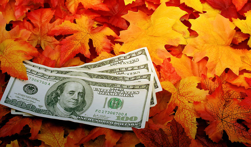 Four one hundred dollar bills sitting on a fall leaf background, money