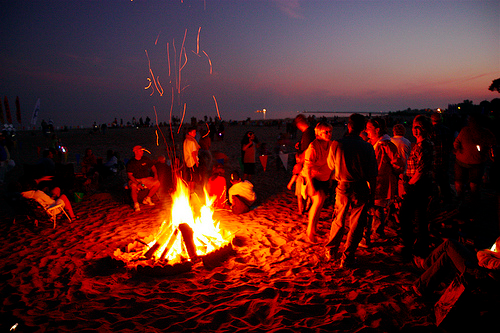 new year party goers gathering around a bonfire at the beach