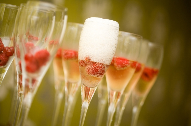 champagne glasses with raspberries inside them ready for toasting the new year